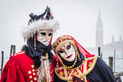 Couple in red costumes pose at the Venice Carnival Stock Photo