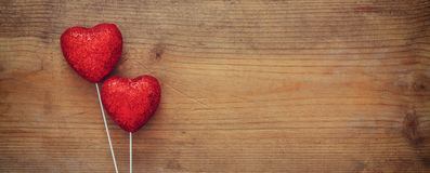 Couple of red glitter hearts on wooden background Royalty Free Stock Images