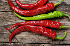 A couple of Red and green  chili peppers. Closeup of red Hot chili pepper pod on a wooden desk Royalty Free Stock Images