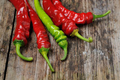 A couple of Red and green  chili peppers. Closeup of red Hot chili pepper pod on a wooden desk Royalty Free Stock Photo