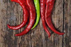 A couple of Red and green  chili peppers. Closeup of red Hot chili pepper pod on a wooden desk Royalty Free Stock Image