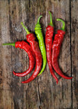 A couple of Red and Green chili peppers. On a wooden desk Royalty Free Stock Photo
