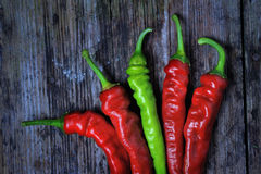 A couple of Red and Green chili peppers. On a wooden desk Royalty Free Stock Photos