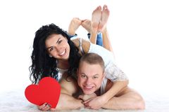 Couple with red heart lie on the floor Stock Images