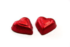 A couple of red hearts. A couple of red foil wrapped heart shape chocolates for valentines day with white background, a symbol of love and sweet Stock Photography