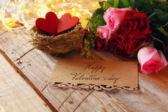 Couple of red hearts in the nest on wooden table Royalty Free Stock Image