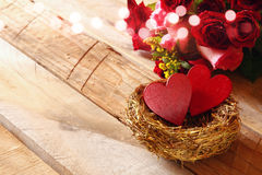 Couple of red hearts in the nest on wooden table Stock Image
