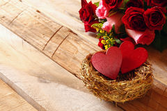 Couple of red hearts in the nest on wooden table Royalty Free Stock Photos