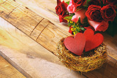 Couple of red hearts in the nest on wooden table Stock Photo