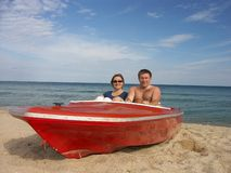 Couple in red motorboat. Young couple sitting in a red motorboat on a beach stock photography
