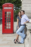 Couple & Red Phone Box in London, England. Romantic man and woman couple next to traditional red telephone box in Westminster, London, England, Great Britain Royalty Free Stock Photography
