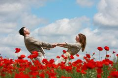 Couple on red poppies field Stock Images
