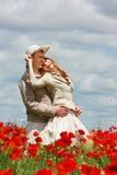 Couple on red poppies field Stock Photography
