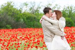 Couple on red poppies field Royalty Free Stock Photos