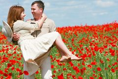 Couple on red poppies field Stock Photo