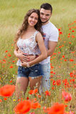 Couple in red poppies Royalty Free Stock Image