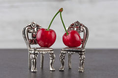 A couple of red ripe cherries on miniature silver chairs. Stock Photo