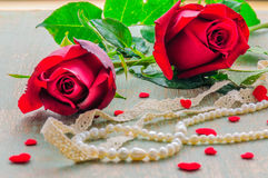 Couple of red rose with heart and pearl ornament decoration. Photo is focused at the right rose Stock Photography