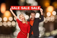 Couple with red sale sign over christmas lights royalty free stock image