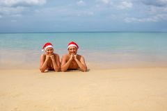 Couple in red Santa hats at tropical beach Royalty Free Stock Photography