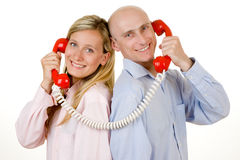 Couple with red telephones Royalty Free Stock Image