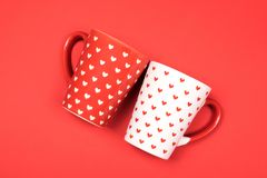Couple of beautiful cups on red. Couple of red and white cups painted with hearts on vibrant background. Valentines day romantic dating concept. Mugs concept royalty free stock photo