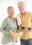 Couple With Red Wineglass And Salad At Home. Portrait of happy senior couple with red wineglass and salad at home Royalty Free Stock Photo