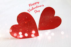 Couple of red wooden hearts. Glitter overlay Royalty Free Stock Image