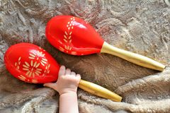 Couple of red wooden maracas and baby hand Royalty Free Stock Photo