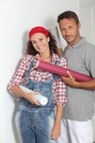 Couple reforming home. Couple standing in their home with paperwall rolls Royalty Free Stock Photo