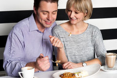 Couple rejoicing their meal in food court stock images