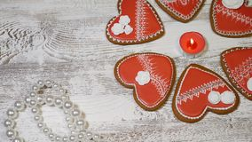 Couple relations concept. St. Valentine Day background. Heart shaped ginger biscuits,burning tea candle and pearl beads. On wooden background. 4k stock footage