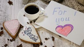 Couple relations. St Valentine Day concept. A cup of coffee and ginger biscuit with knitting needle and yarn on wooden. Background. hand puts For You message stock video footage
