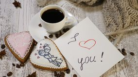 Couple relations. St Valentine Day concept. A cup of coffee and ginger biscuit with knitting needle and yarn on wooden. Background. Hand puts I Love You message stock video