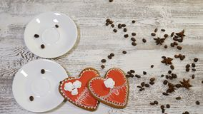 Couple relations. St Valentine Day concept. Top view of two cups of coffee held by female and male hands with heart. Shaped ginger biscuit on wooden background stock video