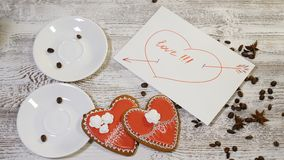 Couple relations. St Valentine Day concept. Top view of two cups of coffee held by female and male hands with heart. Shaped ginger biscuit on wooden background stock video footage