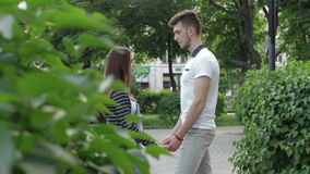 A couple in a relationship holding hands and talking in the Park stock footage