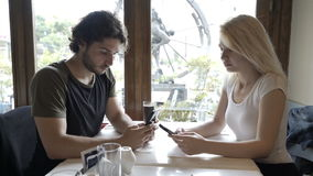 Couple with relationship issues networking on social media using smartphones sitting at table in restaurant stock footage