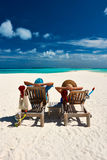 Couple relax on a beach at christmas Stock Images