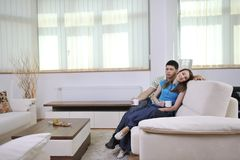 Couple relax at home on sofa in living room Stock Image