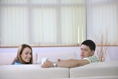 Couple relax at home on sofa in living room. Happy young couple relax at home in modern and bright living room Royalty Free Stock Photography