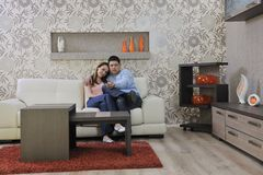Couple relax at home on sofa in living room. Happy young couple relax at home in modern and bright living room Stock Images