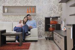 Couple relax at home on sofa in living room. Happy young couple relax at home in modern and bright living room Royalty Free Stock Photos
