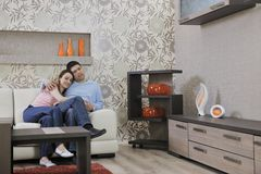 Couple relax at home on sofa in living room. Happy young couple relax at home in modern and bright living room Stock Image