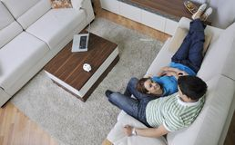 Couple relax at home on sofa in living room. Happy young couple relax at home in modern and bright living room Stock Photography