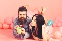 Couple relax in morning with coffee. Couple in love drink coffee in bed. Man and woman in domestic clothes, pajamas royalty free stock image