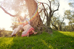 Couple relax under the tree. Fine art style. Olive garden. Stock Images
