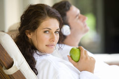 Couple relaxaing on deck chairs, portrait of woman holding green apple, close-up Royalty Free Stock Photos