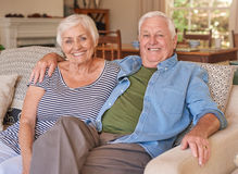 Couple of relaxed seniors sitting on their couch Stock Photos