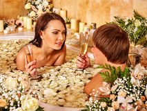Couple relaxes in the bath with flower petals. SPA-center Royalty Free Stock Photos
